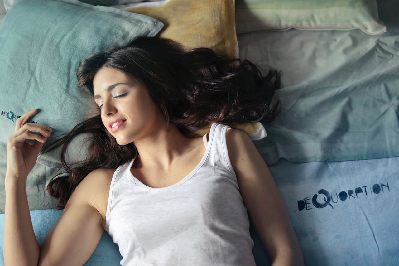 Woman laying on the bed sleeping with a smile on her face.