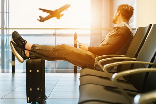 A man sitting in an airport terminal with his feet up on a suitcase, watching an airplane take off.